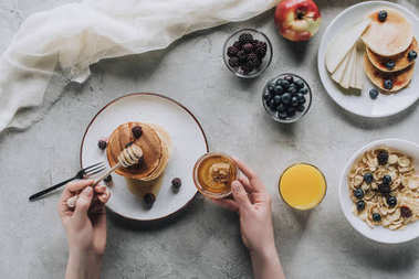cropped shot of person eating delicious homemade pancakes with honey and fruits on grey