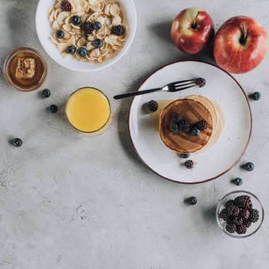 top view of sweet gourmet breakfast with pancakes, fruits, honey and muesli on grey