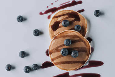 top view of delicious sweet homemade pancakes with fresh blueberries and jam on grey