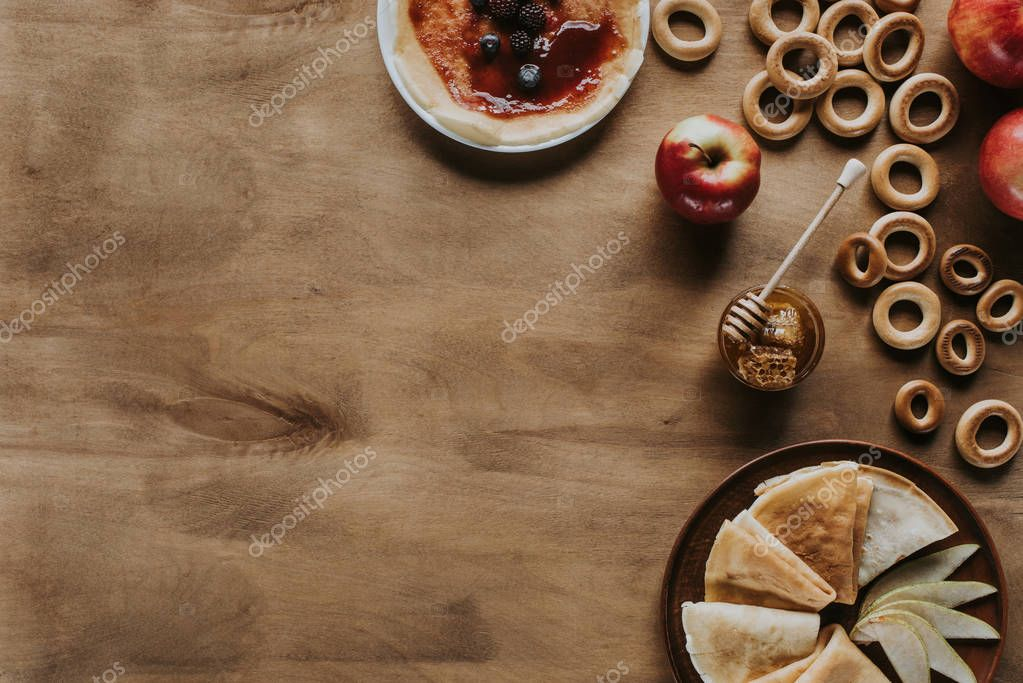 top view of tasty pancakes with apples, berries, honey and bagels on wooden table