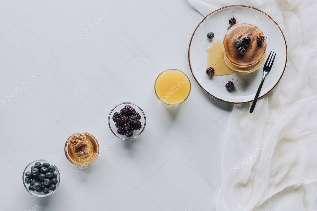 top view of tasty breakfast with pancakes, berries, honey and juice on grey