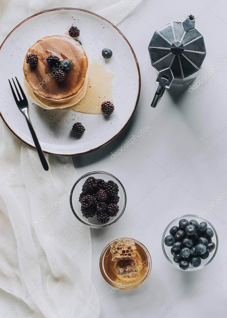 top view of tasty breakfast with pancakes, berries, honey and coffee on grey