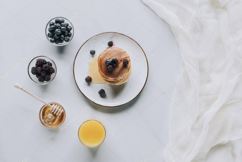 top view of sweet tasty pancakes with honey, berries and juice on grey