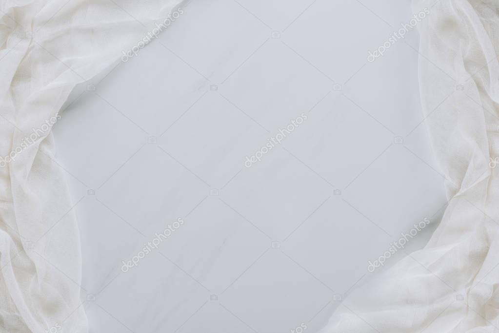 top view of white fabric and blank grey background
