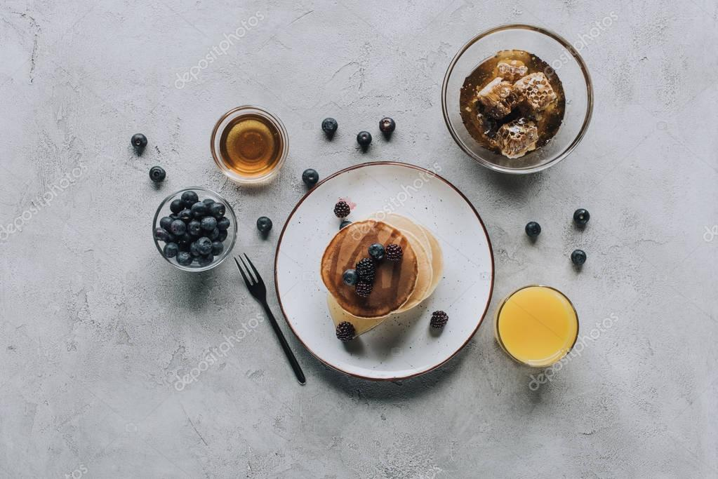 top view of gourmet pancakes with fresh berries, juice and honey on grey