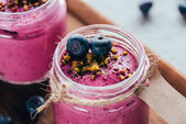 Fotografie close-up view of sweet healthy smoothie with granola, nuts and berries