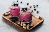 gesunder Gourmet-Smoothie in rosa mit Müsli, Nüssen und Beeren