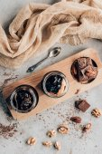 Photo top view of sweet desserts in glass jars and chocolate pieces on wooden board