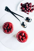 top view of sweet tasty cherry dessert in glass jars on white