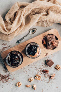 top view of sweet desserts in glass jars and chocolate pieces on wooden board