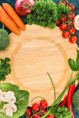 top view of fresh healthy raw vegetables and empty wooden plate