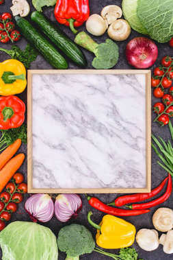 top view of fresh raw vegetables and blank marble board on black