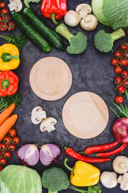 top view of empty wooden plates and fresh raw vegetables on black