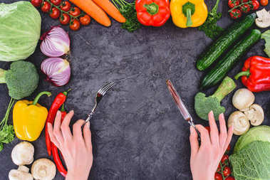 cropped shot of hands holding fork and knife above healthy fresh vegetables on black