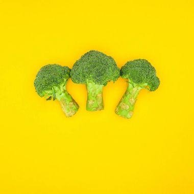 top view of fresh green organic broccoli isolated on yellow