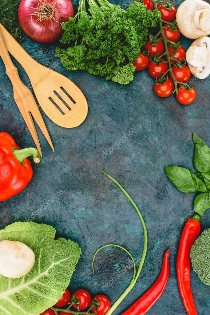 top view of fresh healthy vegetables and wooden utensils on black