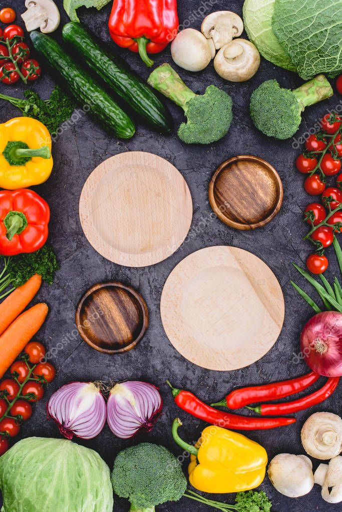 top view of empty wooden plates and fresh raw organic vegetables on black