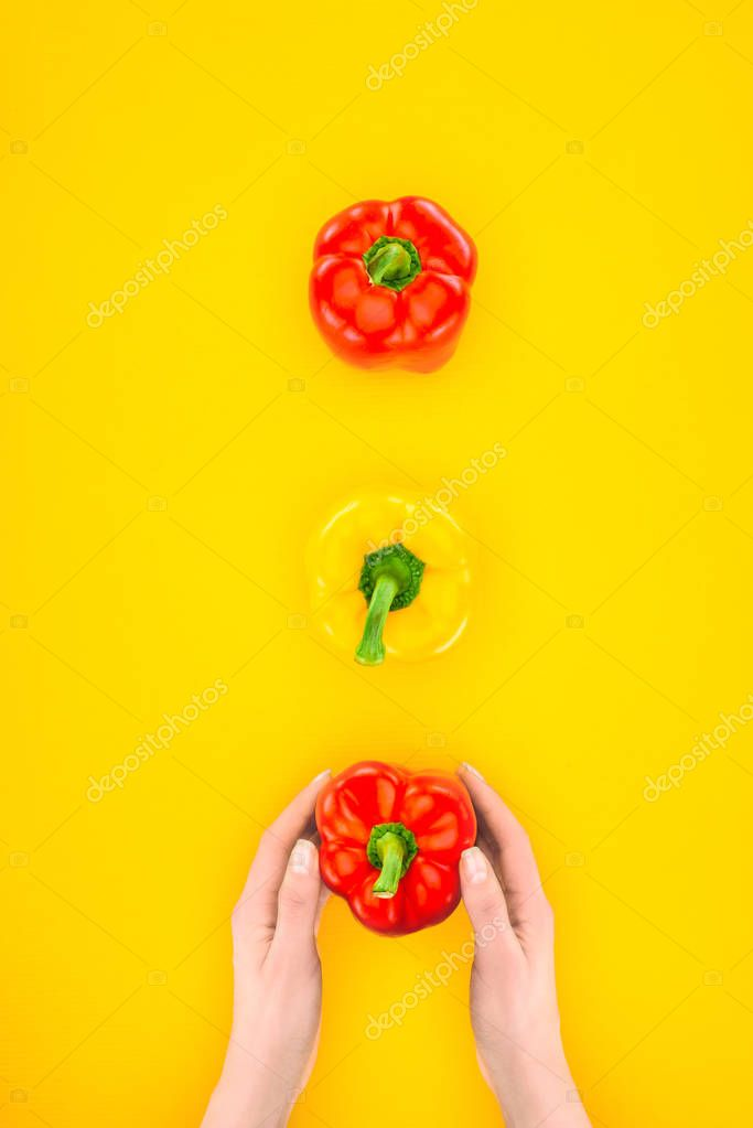 top view of human hands and fresh raw peppers isolated on yellow