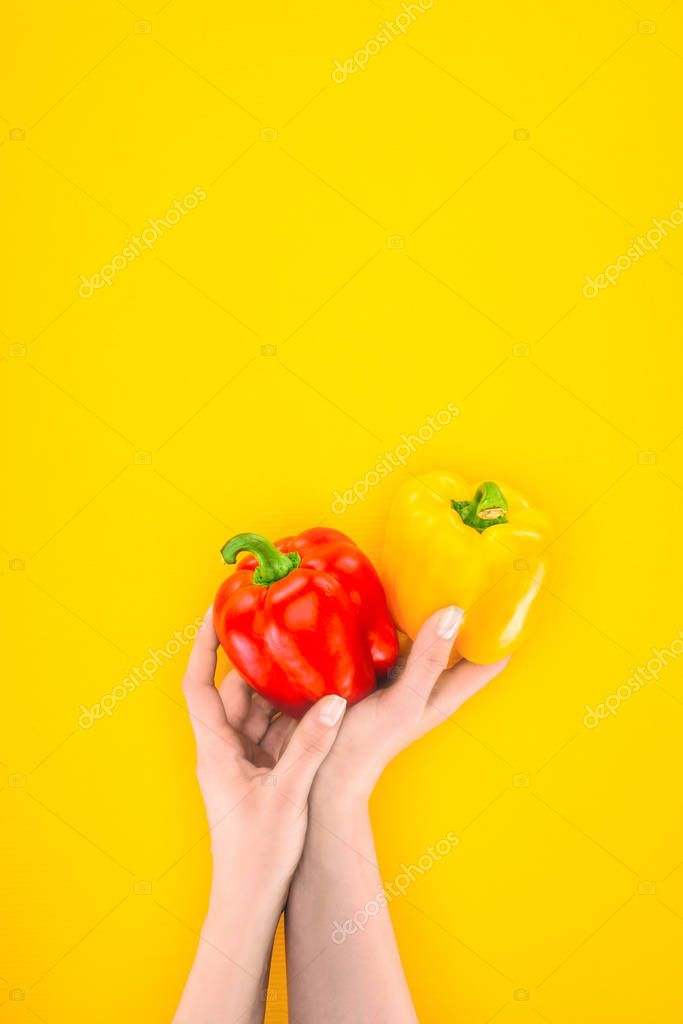 cropped shot of person holding fresh organic peppers in hands isolated on yellow