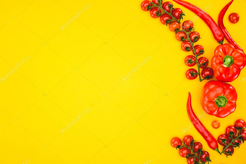 top view of fresh raw peppers and cherry tomatoes isolated on yellow
