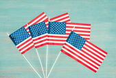 flat lay with arranged american flags on blue wooden surface, presidents day concept
