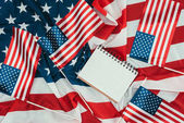Photo top view of arranged american flags and blank notebook, presidents day concept