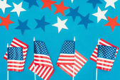 Photo top view of arranged stars and american flags isolated on blue, presidents day celebration concept