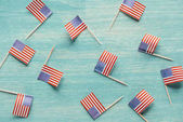 Fotografie top view of arranged american flags on blue wooden surface, presidents concept