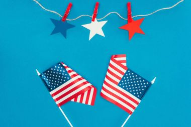 top view of arranged stars and american flags isolated on blue, presidents day celebration concept