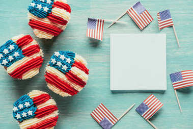 flat lay with arranged cupcakes and american flags on wooden tabletop, presidents day celebration concept