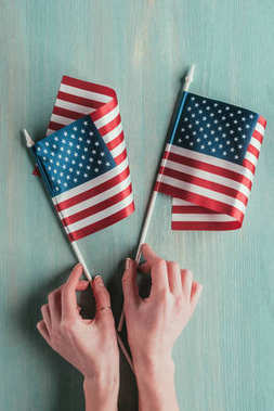partial view of woman holding american flags in hands on blue wooden tabletop, presidents day concept