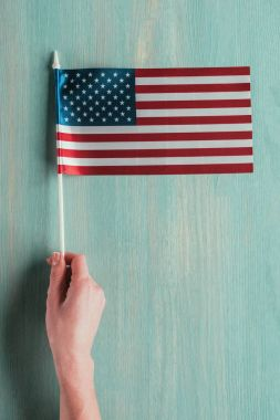 partial view of woman holding american flag in hand on blue wooden tabletop, presidents day concept