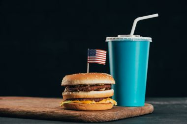 close up view of burger with american flag and soda drink, presidents day celebration concept