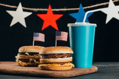 close up view of burgers with american flag and soda drink, presidents day celebration concept
