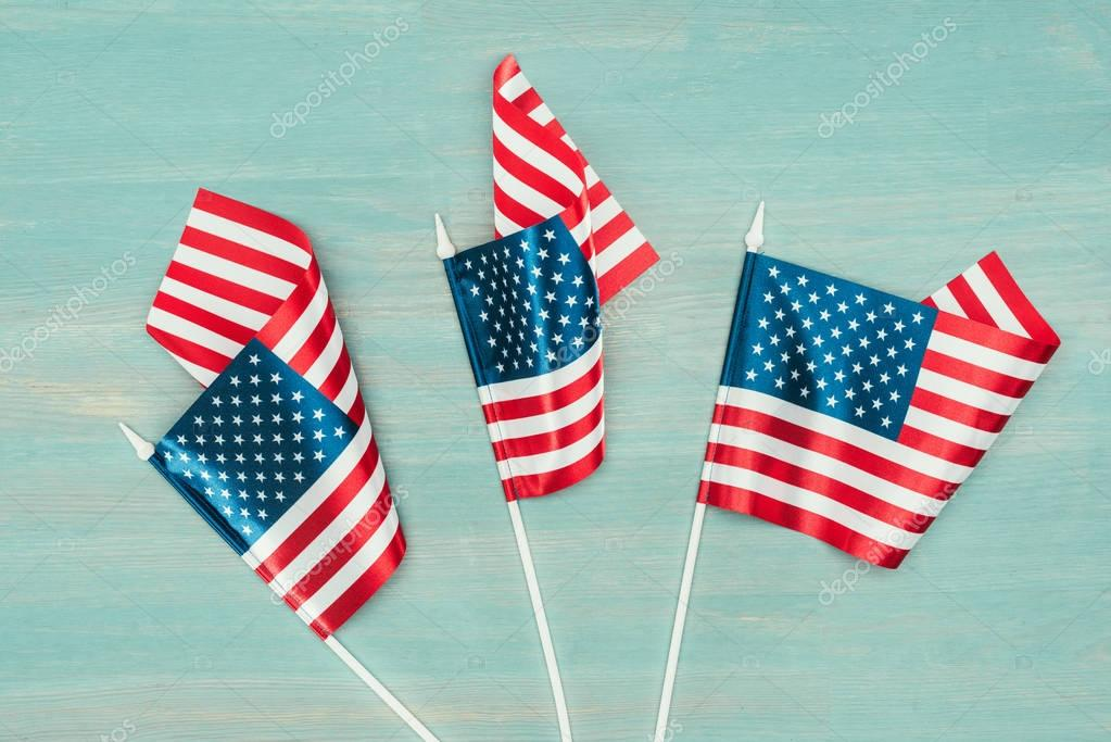 top view of arranged american flags on blue wooden surface, presidents day concept