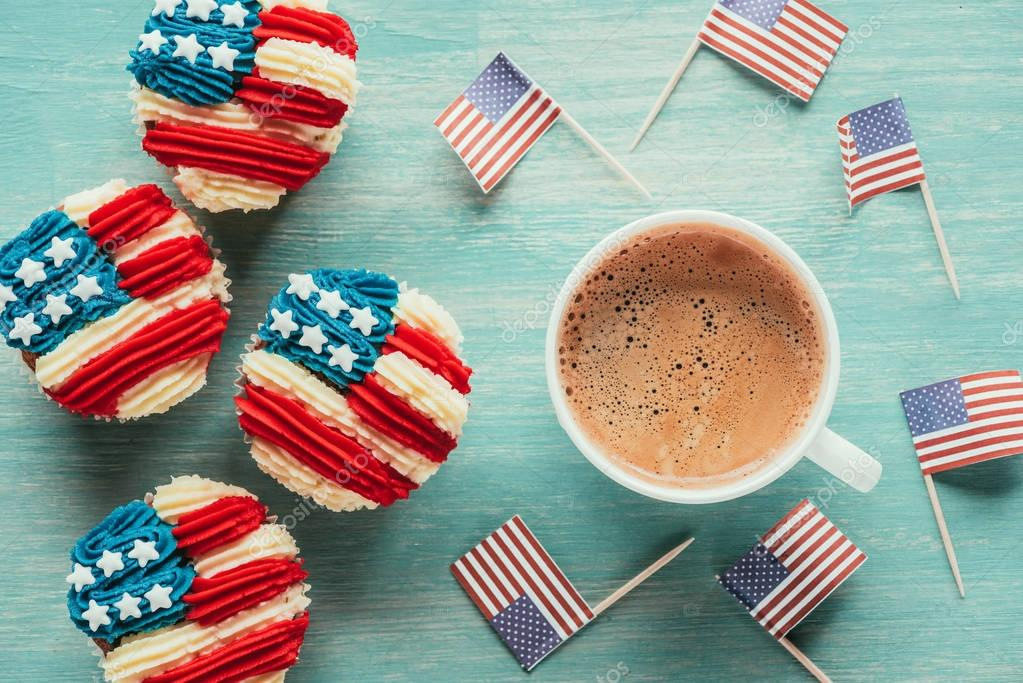 flat lay with arranged cupcakes, cup of coffee and american flags on wooden tabletop, presidents day celebration concept