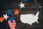 Fotografie top view of arranged american flags, piece of map and stars on wooden surface, presidents day celebration concept
