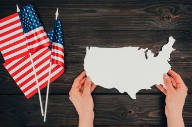 top view of arranged american flags and female hands with piece of blank map on wooden tabletop, presidents day concept