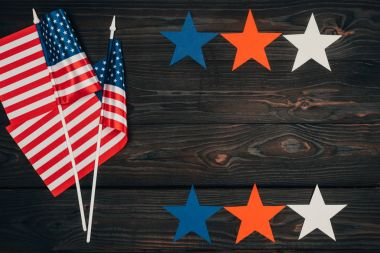 top view of arranged american flags and stars on wooden surface, presidents day celebration concept