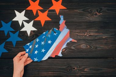 cropped shot of stars and female hand with piece of map with american flag on wooden tabletop, presidents day concept