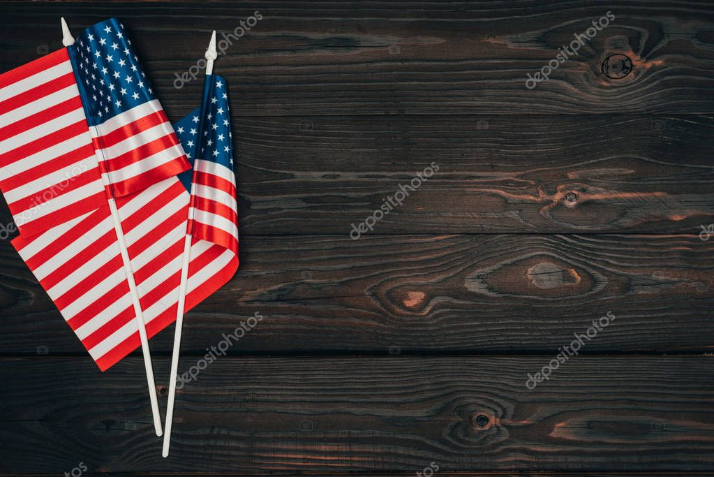 top view of arranged american flags on dark wooden surface, presidents day celebration concept