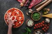 oříznutý snímek ženy šíření kousky mozzarelly na pizzu na konkrétní tabulce