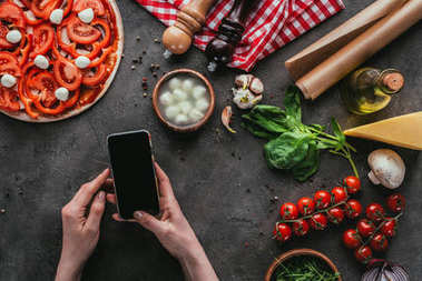 cropped shot of woman using smartphone while preparing pizza on concrete table