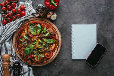 top view of freshly baked pizza with notebook and smartphone on concrete table