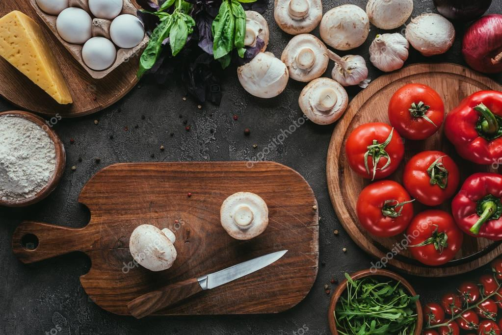top view of different raw ingredients for pizza and knife on concrete surface
