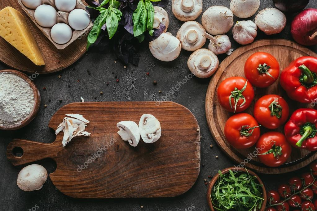 top view of different raw ingredients for pizza on concrete surface