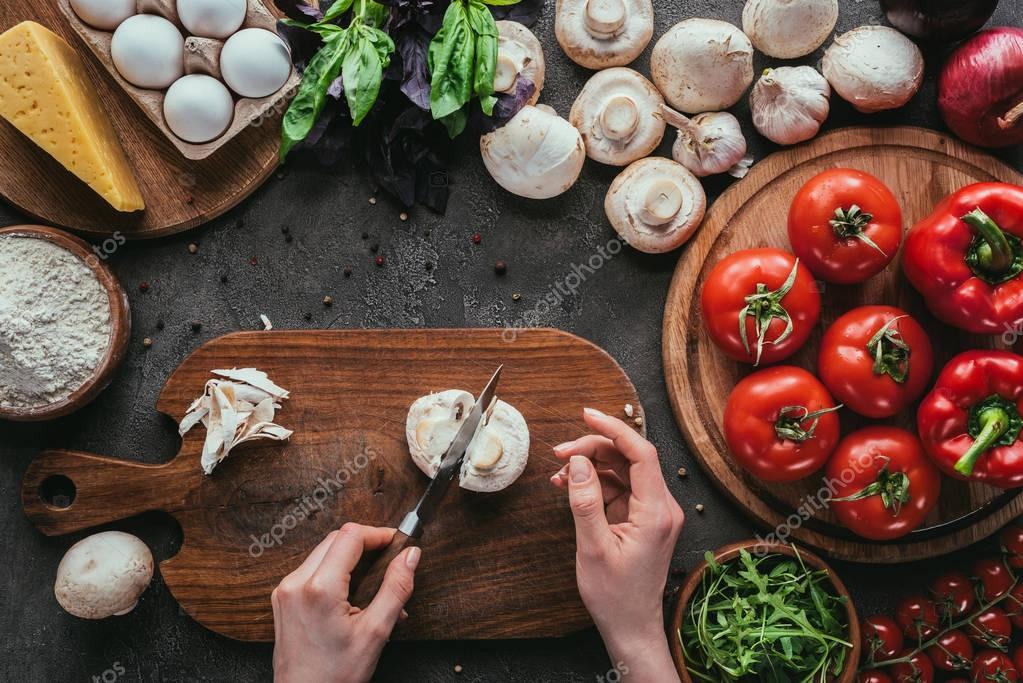 cropped shot of woman cutting mushrooms for pizza on concrete table