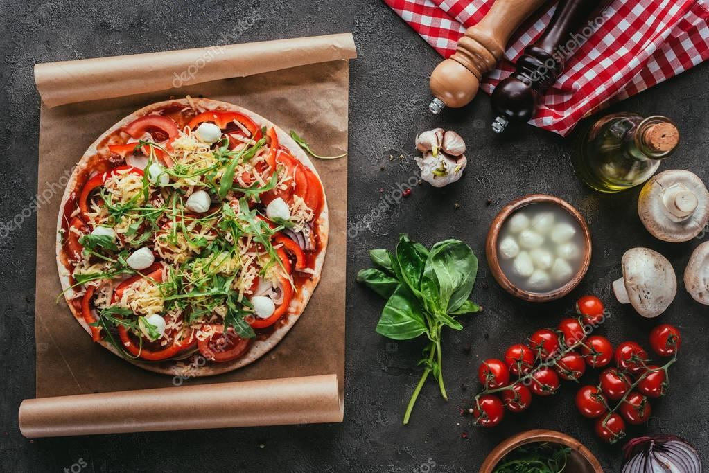 top view of delicious pizza with ingredients on concrete table