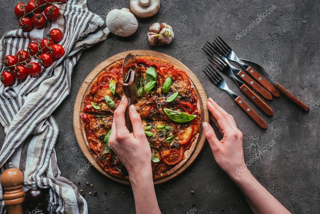 top view of slicing pizza with circle cutter on concrete table