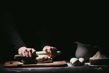 cropped shot of person preparing dough with rolling pin on black